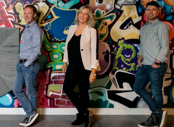 Karl Tapley, Michelle Fogarty, and James Brogan of PepTalk stand next to each other in front of a wall with graffiti on it.