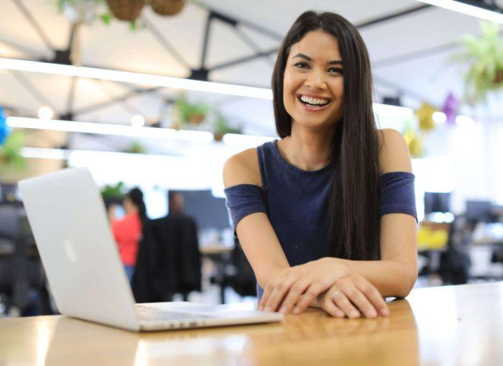 Canva CEO Melanie Perkins smiling and sitting at a table with a laptop in front of her.