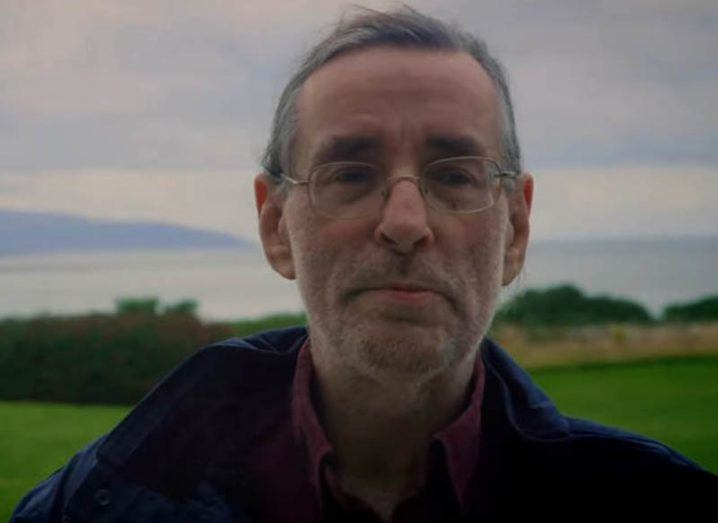 Headshot of professor Dave Reid smiling with hilly landscape in the background.