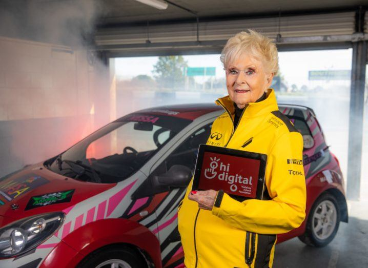 """Photo of an older woman in yellow racing gear holding a tablet that reads """"Hi Digital"""". There is a race car in the background."""