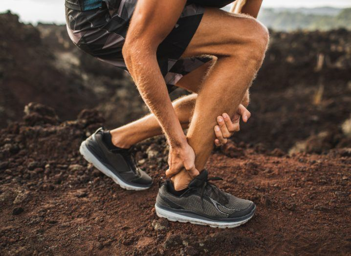 Injured male runner holds his ankle while running outdoors.