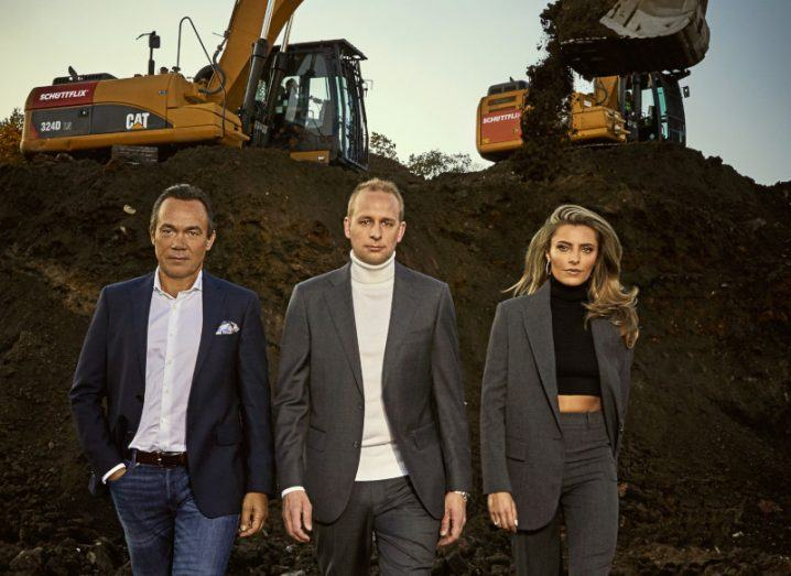 Two men and one woman from the Schüttflix team with a construction site and machinery in the background.