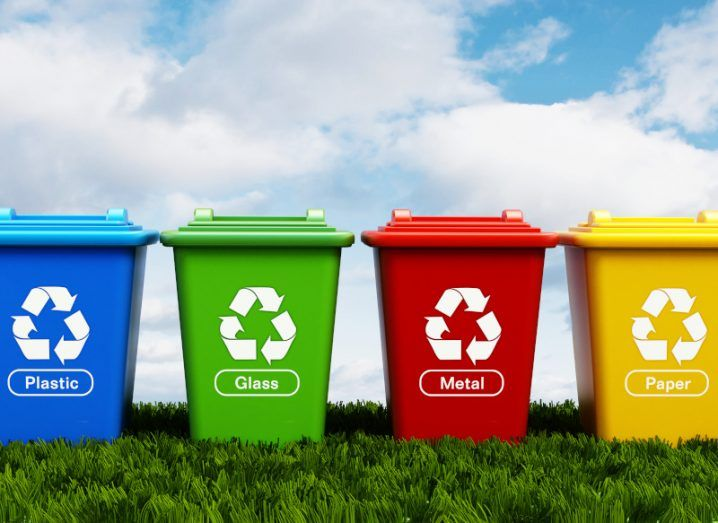 Plastic, glass, metal and paper recycling bins standing on green grass.