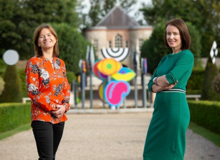 Dr Ruth Barnes and Martina Skelly stand in a garden outside a building, smiling at the camera.