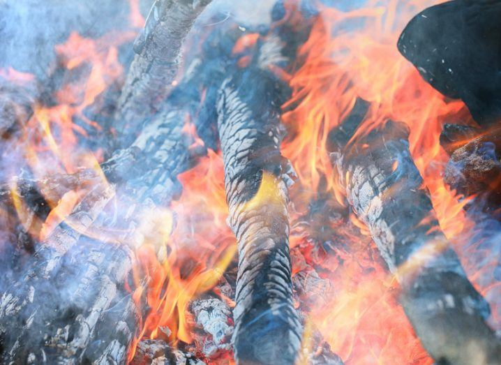 Wood is burning in a smoky fire with orange flames.