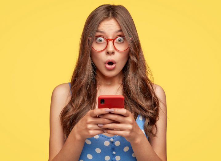 Woman holding a mobile phone in her hands and looking surprised against a yellow background.