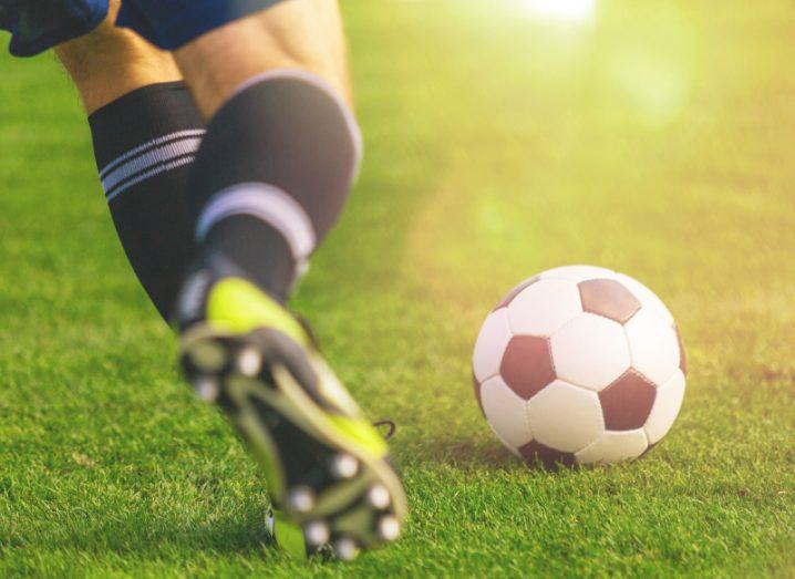 A football player is about to kick the ball. Only his feet and lower legs are visible.