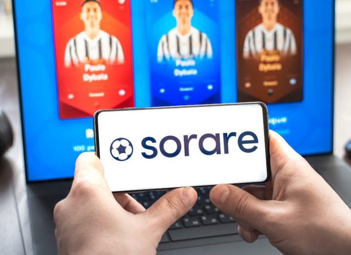 Sorare logo on a smartphone held by hands with a laptop screen showing player cards in the background.