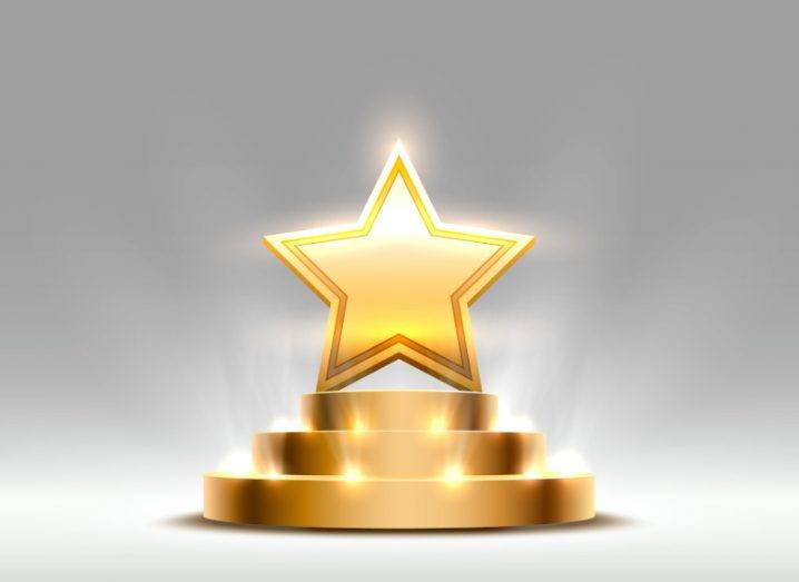 An artist's digital depiction of a golden star award is shown. The star is on a podium and is lit up by yellow lights, indicating the winners of the Breakthrough Prizes.