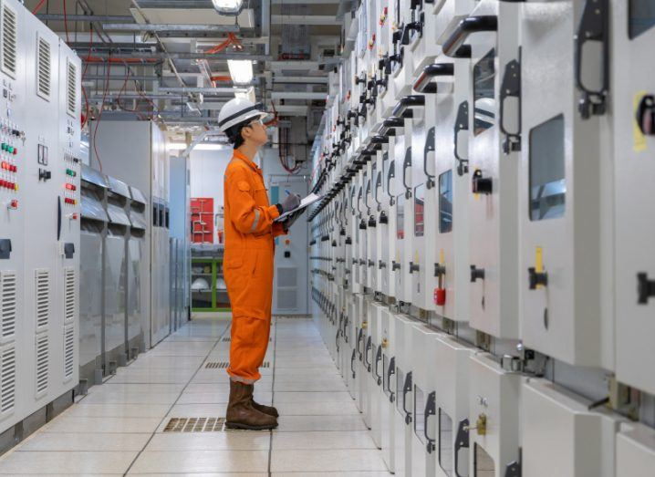 An electrician is standing in front of a high voltage electrical switch board parameter in switchgear room, like the ones at E&I Engineering. He is wearing an orange safety jumpsuit.