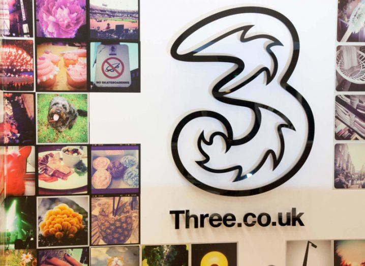 Three logo among assorted pictures on a white wall in the company's store in Maidenhead, UK.