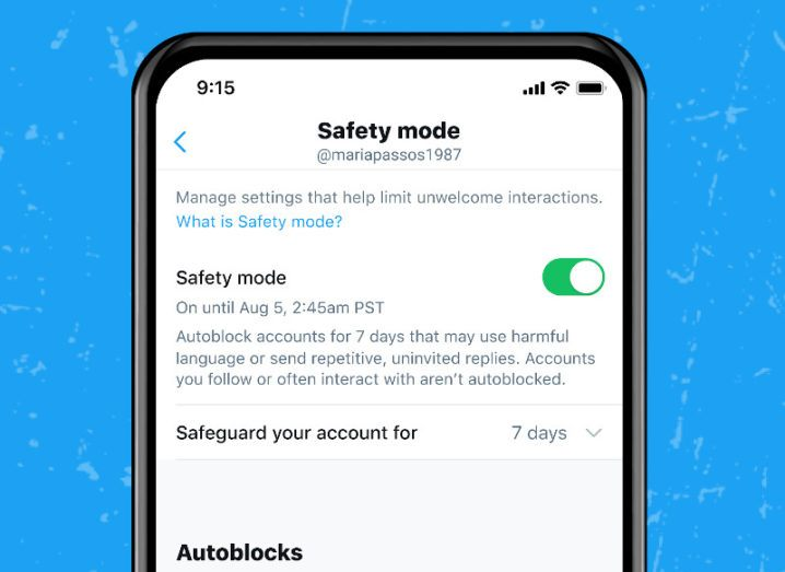 A phone with Twitter's safety mode feature is shown on-screen. The black smartphone is depicted against a blue background.