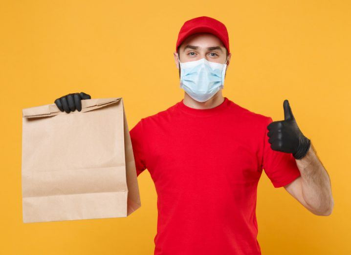 Delivery man holding a bag of food in one hand and gesturing a thumbs-up with the other hand.