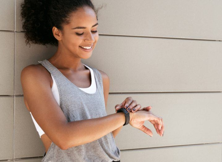 A woman is standing against a wall and smiling. She is in fitness clothes and is adjusting her wearable fitness device.