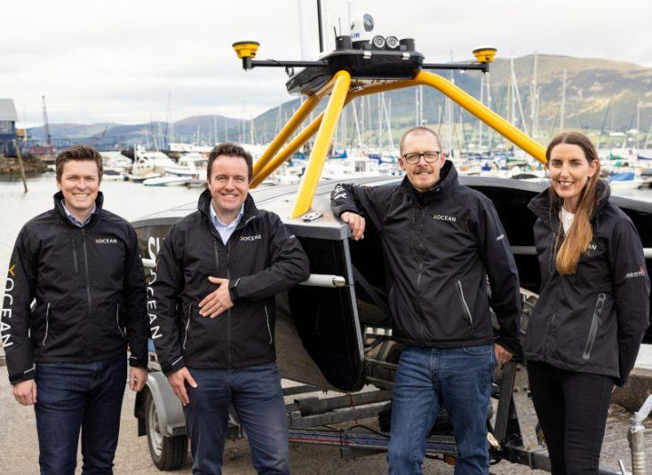 Xocean team members standing in front of an uncrewed surface vessel.