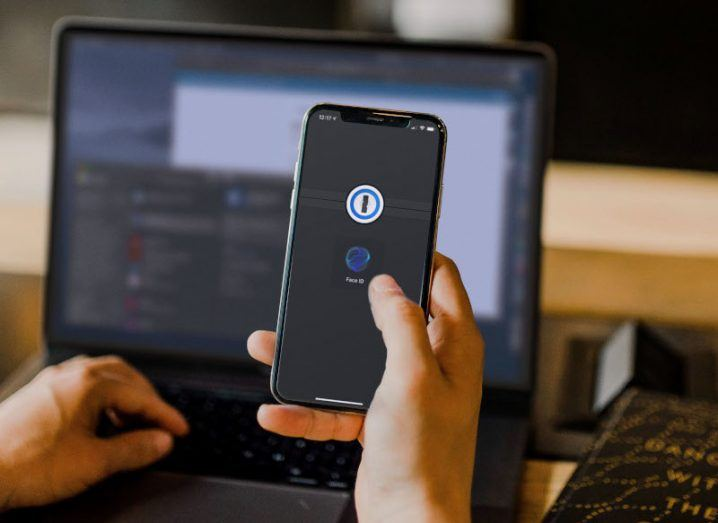A person holding a phone up with the 1Password logo on the screen. Behind that on the desk is a laptop.