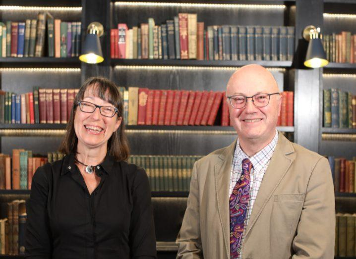 Ann O'Dea and Prof Mark Ferguson stand in front of a tall library wall, adorned with books.