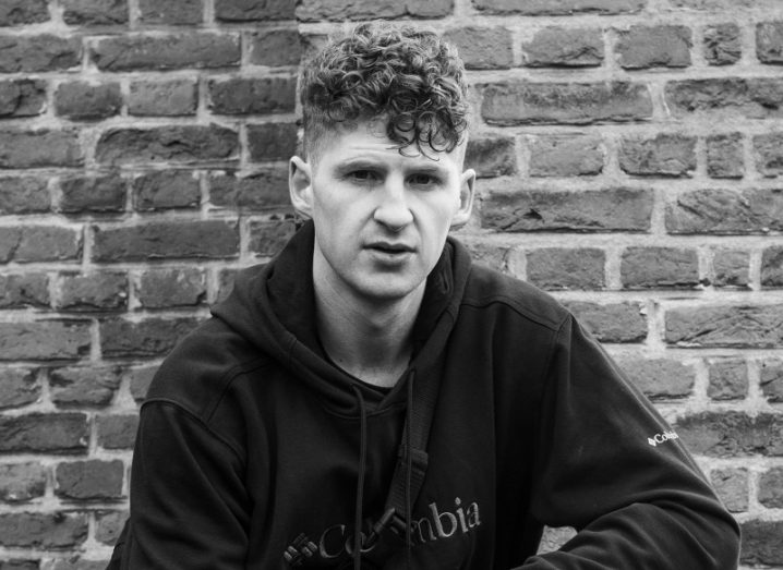 Black-and-white image of a young man with curly hair wearing a dark hoody. He is crouching in front of a brick wall.