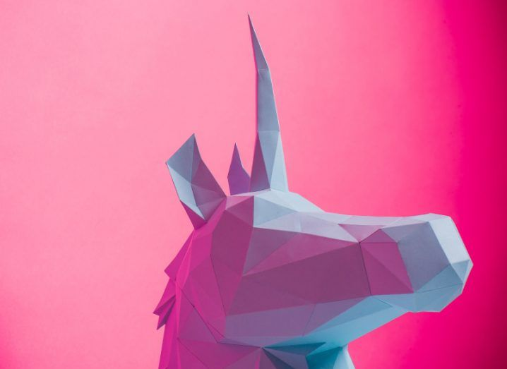 A minimalist graphic of a white unicorn against a bright pink background.