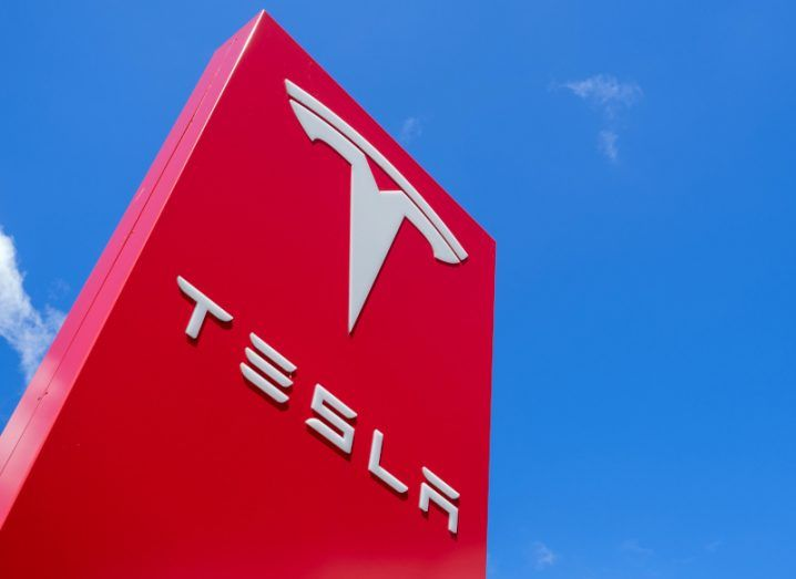 The Tesla logo at one of its dealerships under a bright blue sky.