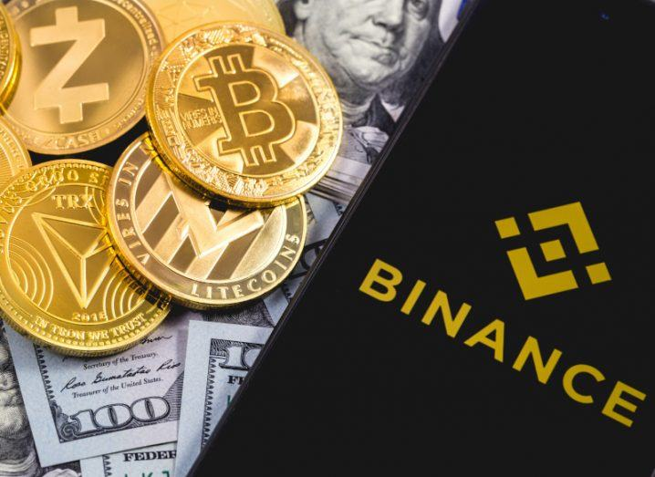 Binance logo is displayed on a smartphone screen, which is resting on a pile of US dollar notes and gold bitcoins.