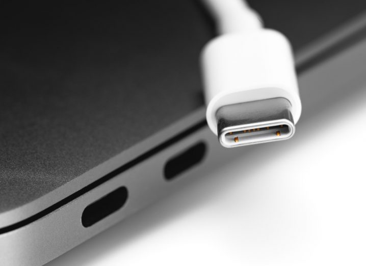 A USB-C cable next to a compatible port on a laptop.