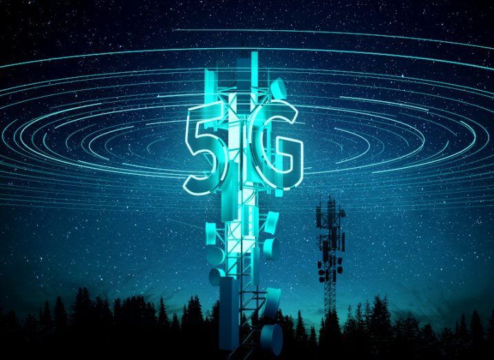 5G mast glowing in the dark, with a 5G sign illuminated on it and glowing signals surrounding it.