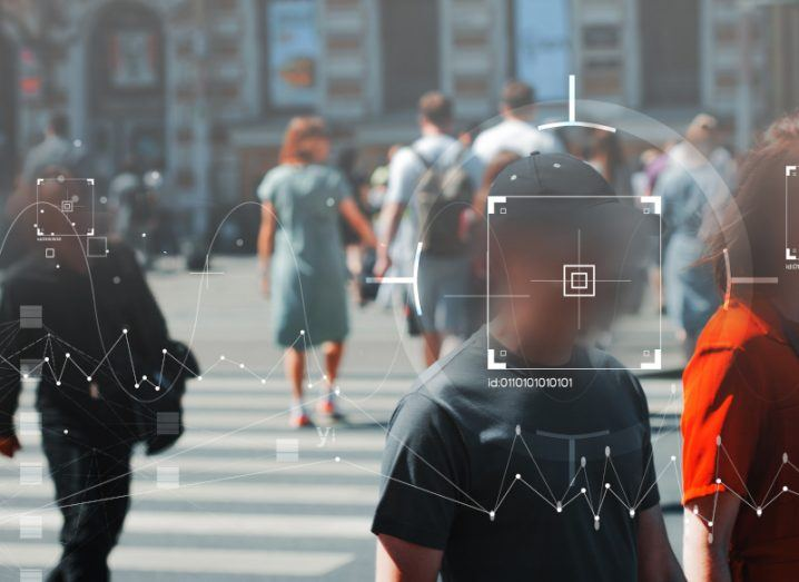 People under surveillance in the street with their faces blurred and superimposed with targets.