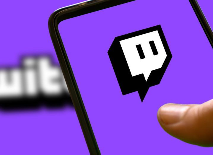 A person's finger on a phone, which has the Twitch logo open on the screen. The purple Twitch branding can also be seen in the background.