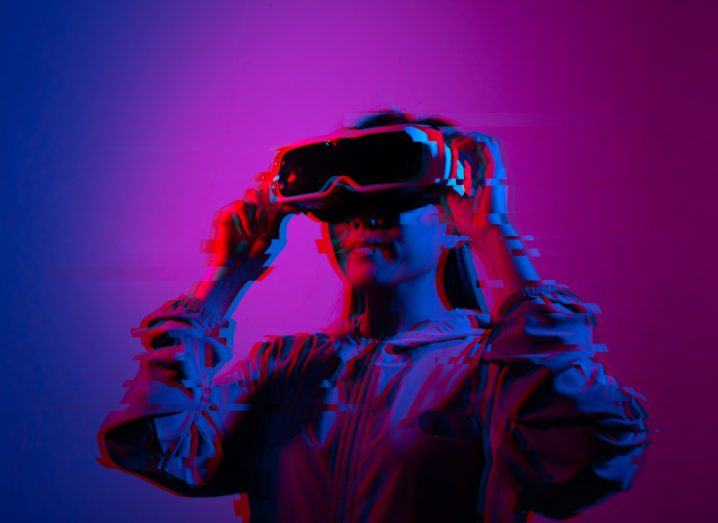 A pink-hued image of a woman wearing a VR headset.