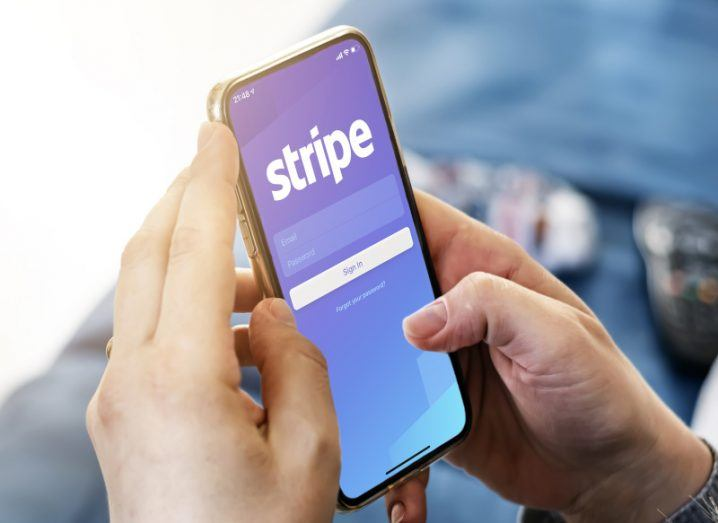 Pair of hands holding a smartphone with Stripe payment company logo displayed on the screen.