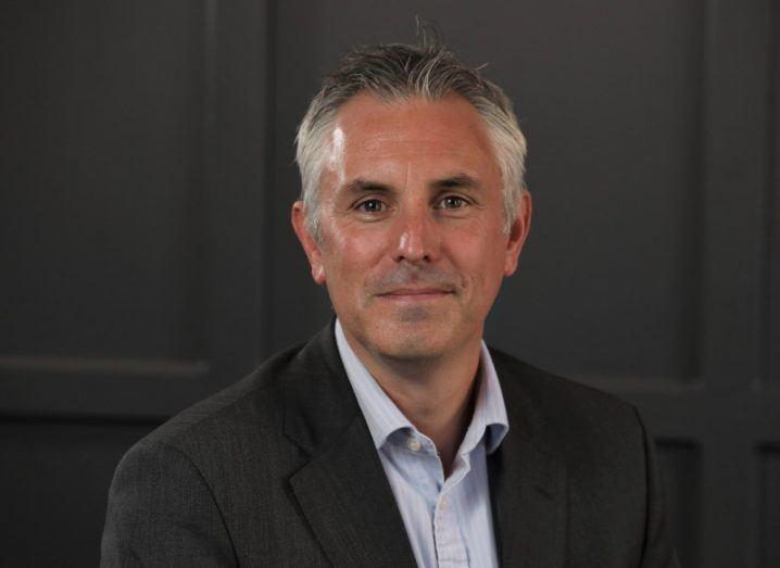 Headshot of Northern Ireland fintech envoy Andrew Jenkins in a dark suit against a dark background.