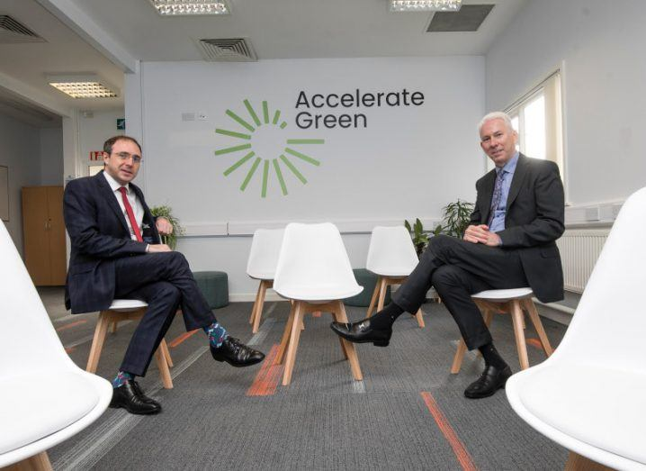 Minister Robert Troy and Tom Donnellan sit in a room on plastic white chairs, with 'Accelerate Green' logo on the wall behind them.