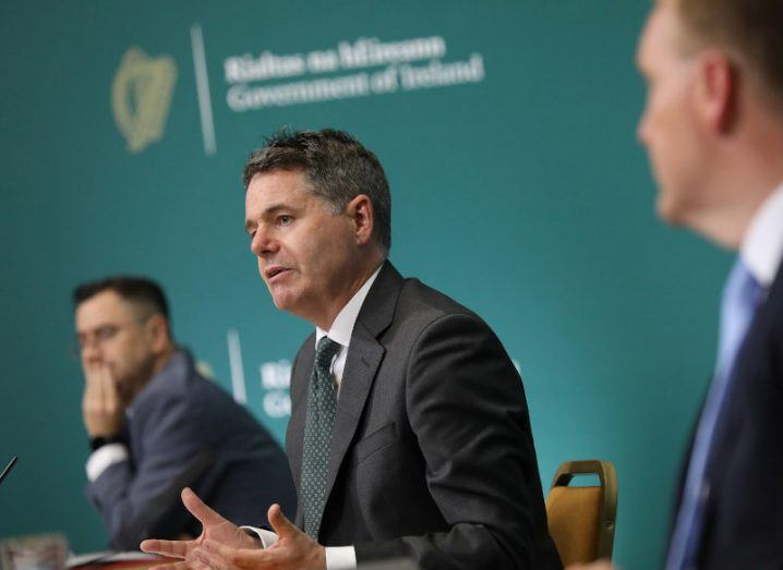 Minister Paschal Donohoe wearing a suit, sitting at a press conference table for Budget 2022.