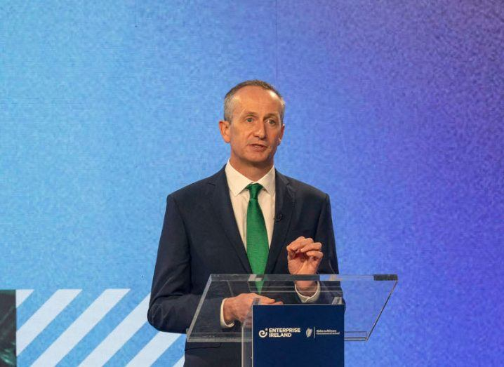 Enterprise Ireland CEO Leo Clancy stands at a clear perspex podium delivering a speech against a textured blue background. He is wearing a dark suit and emerald green tie.