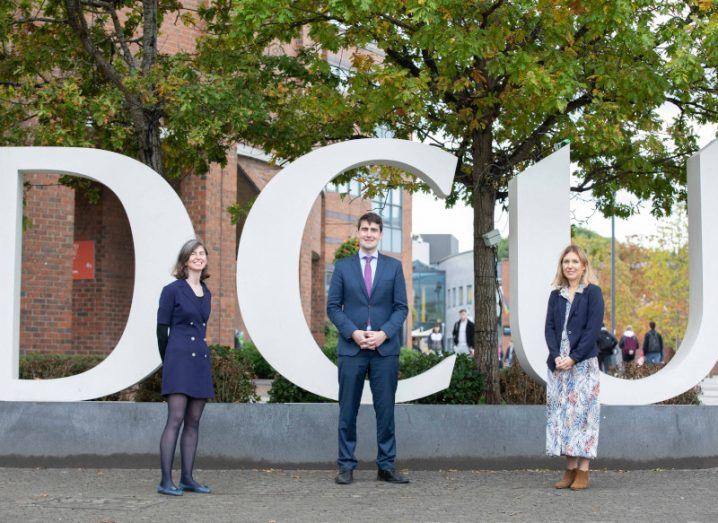 Three people stand in front of a sign that spells out DCU in large, white letters.