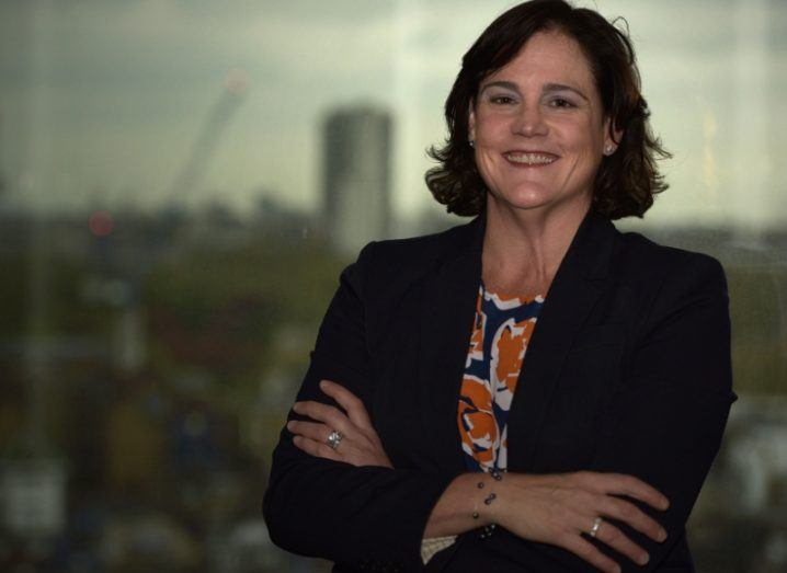 A woman with short brown hair stands with her arms folded smiling at the camera in front of a grey picture of a cityscape.