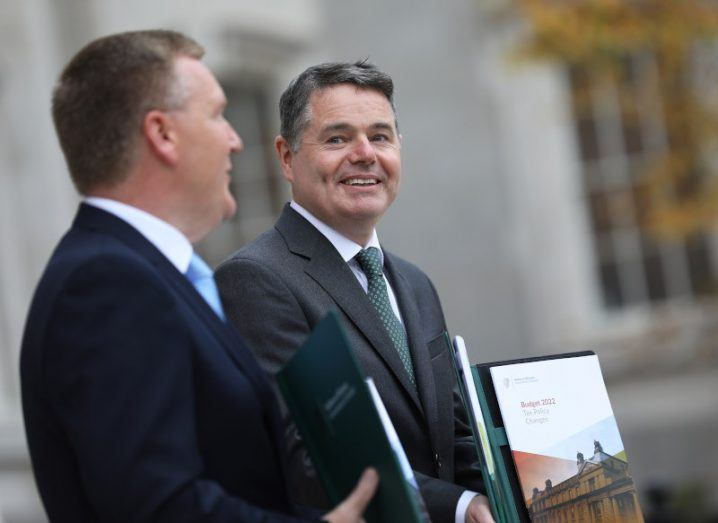 Two men stand outside holding copies of the Budget.