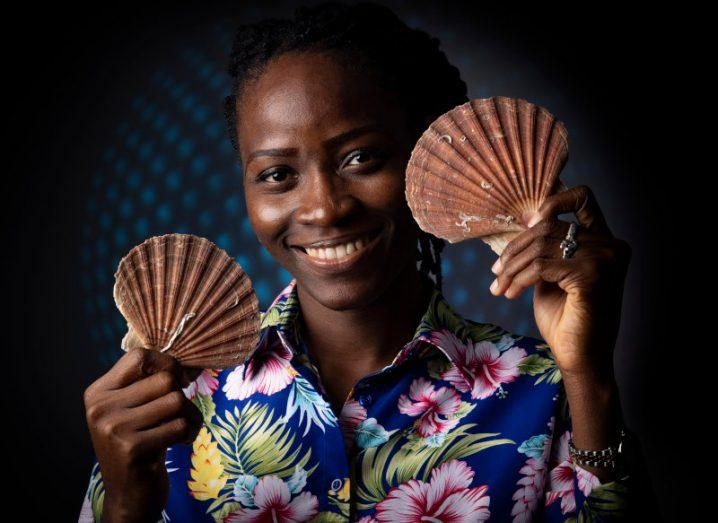 Postgraduate researcher Brakemi Egbedi holds shells up to her face and smiles. Her project focuses on the possible pharmaceutical uses for shell waste.