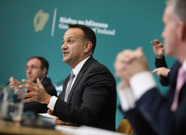 Leo Varadkar sits among a row of Government ministers at a long table, gesturing as he speaks to the press.