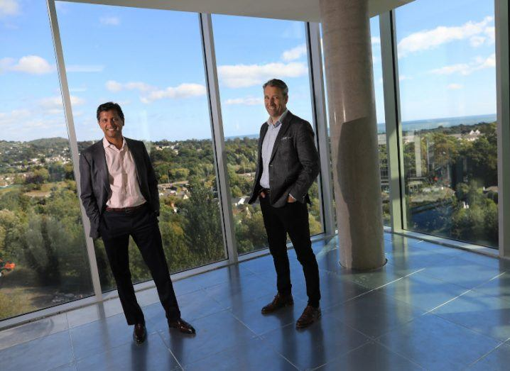 Two men stand in an empty high-rise office space looking out onto a Dublin suburb.