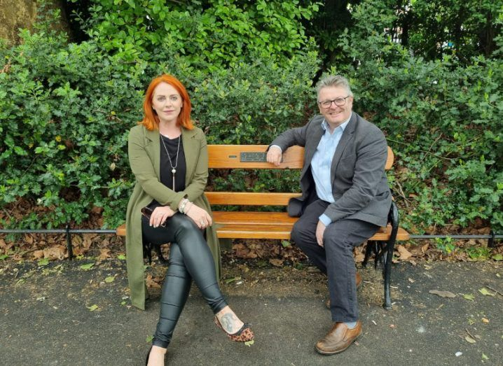 A red-haired woman in black leggings and a long khaki coat sits on a bench alongside a man in a grey suit and pale blue shirt.