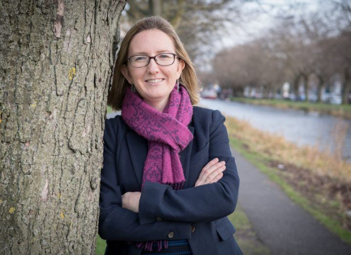 Prof Caitriona Jackman of DIAS wearing a coat and scarf with arms folded leans against a tree, smiling at the camera.