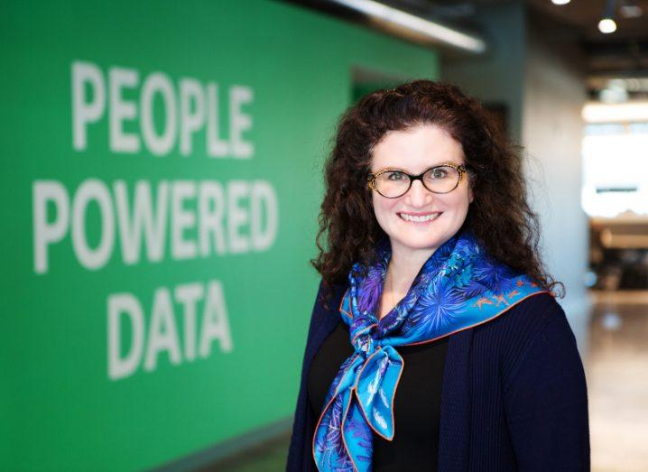 A woman wearing a blue scarf and glasses smiles at the camera. Behind her there is a green wall with white writing that says 'people powered data'.