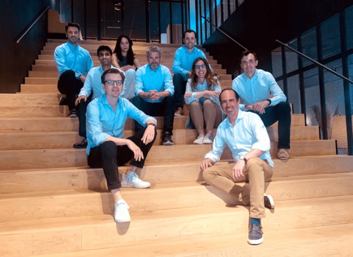 The 2150 team sitting on a wooden stairs in a group.