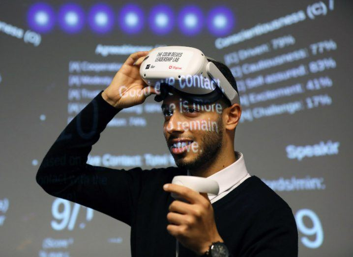 Anas Oudina wearing a VR headset and holding a controller. Light from a projector is on his face and in the background behind him.