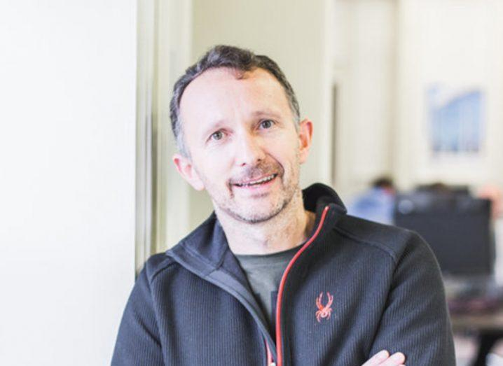 Headshot of Cool Planet CEO Norman Crowley wearing a black jacket and smiling at the camera. Background blurred.