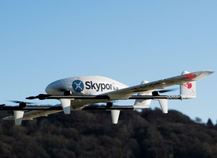 Photo of a white drone in air with the Skyports logo on it.