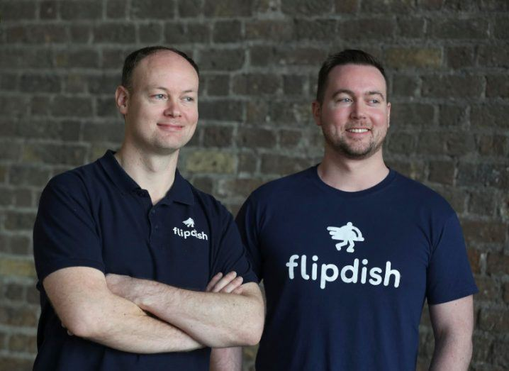 Flipdish co-founders and brothers Conor and James McCarthy wearing Flipdish T-shirts and standing with a brick wall in the background.