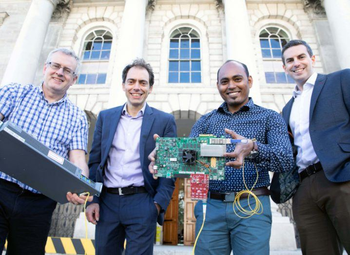 Scientists from Connect and Intel are holding technical equipment and smiling at the camera, with Trinity College Dublin Buildings in the background.